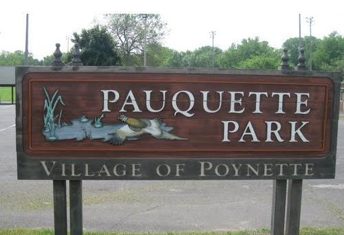 "Wooden sign reading ""Pauquette Park Village of Poynette"" with a pheasant and water depicted"